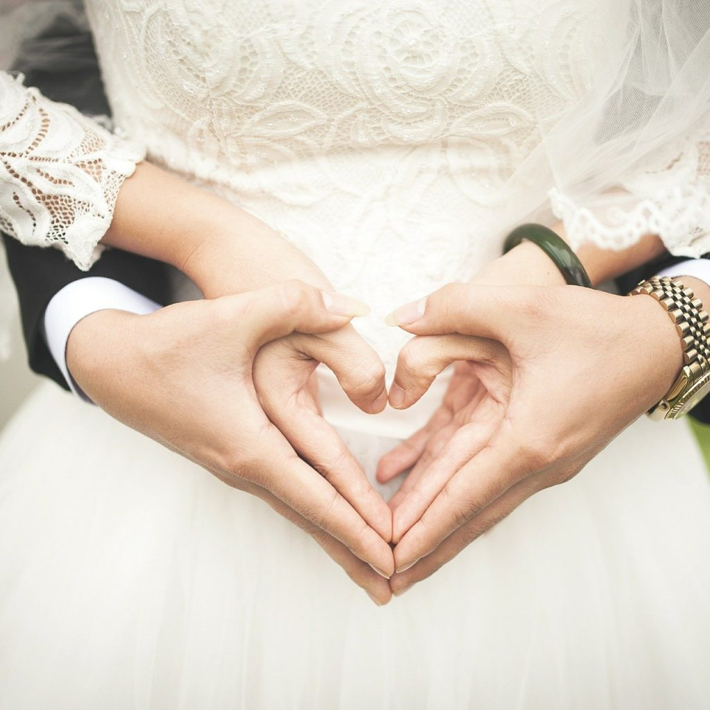 Bride and groom making heart shape with hand