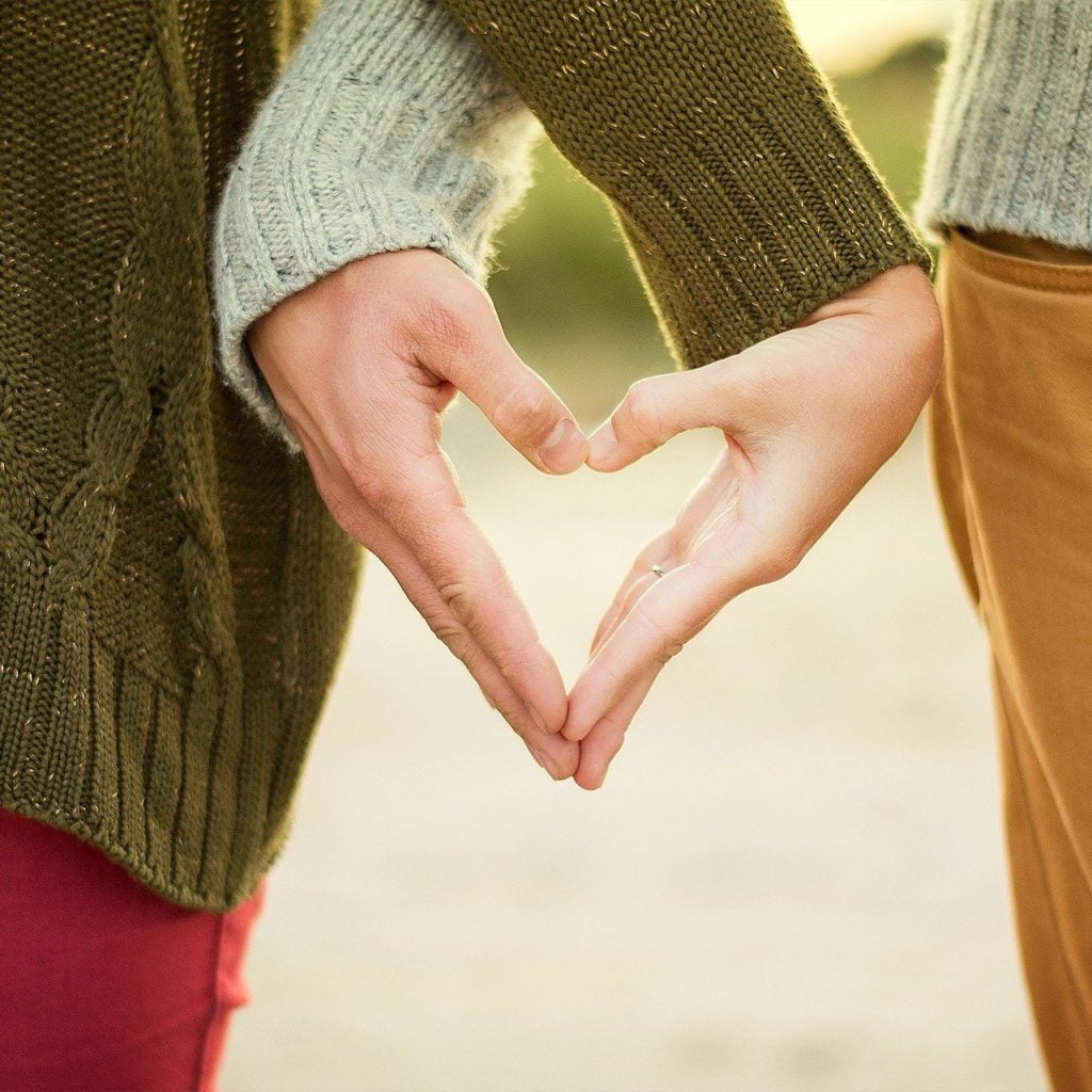 Couple makes heart shape with hands - marriage