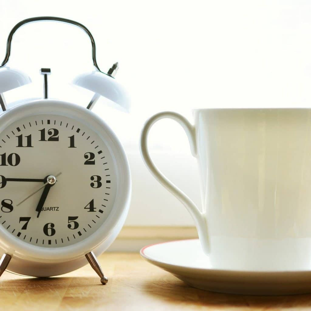 White clock and white tea cup on a table