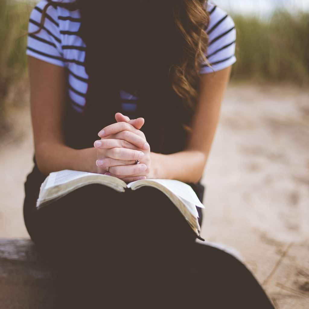 Girl sitting down reading the Bible and praying