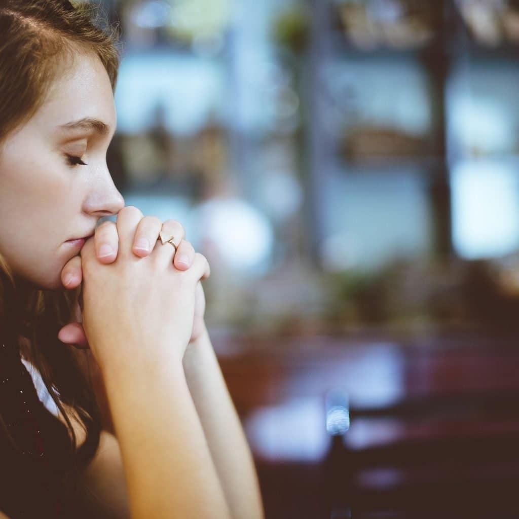 Woman with her hands crossed praying