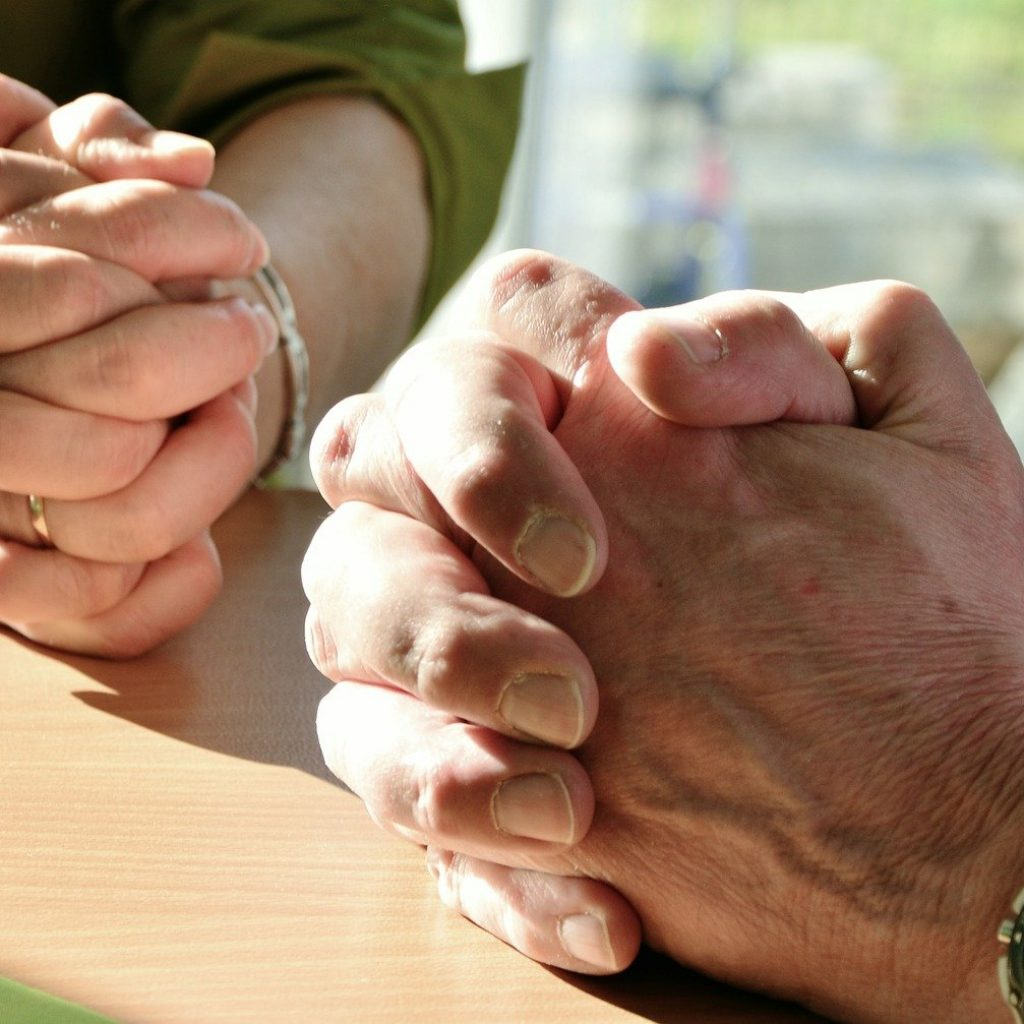 Two people sitting with their hands crossed praying