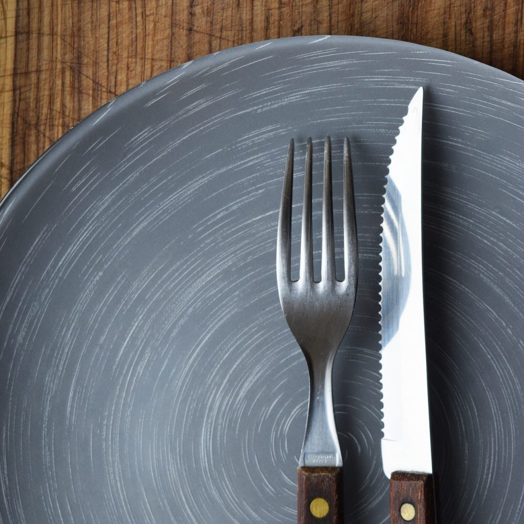 Knife and fork on an empty blue plate