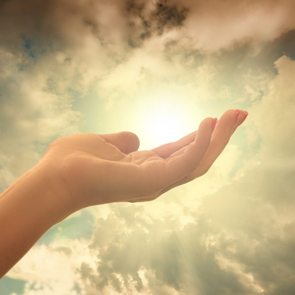 Hand holding the sun in the sky