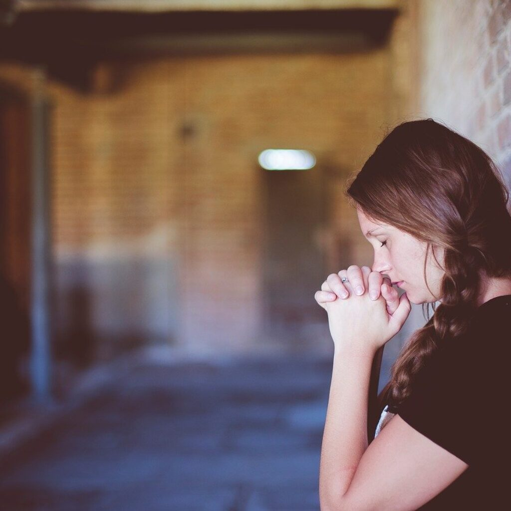 Girl standing by a wall praying