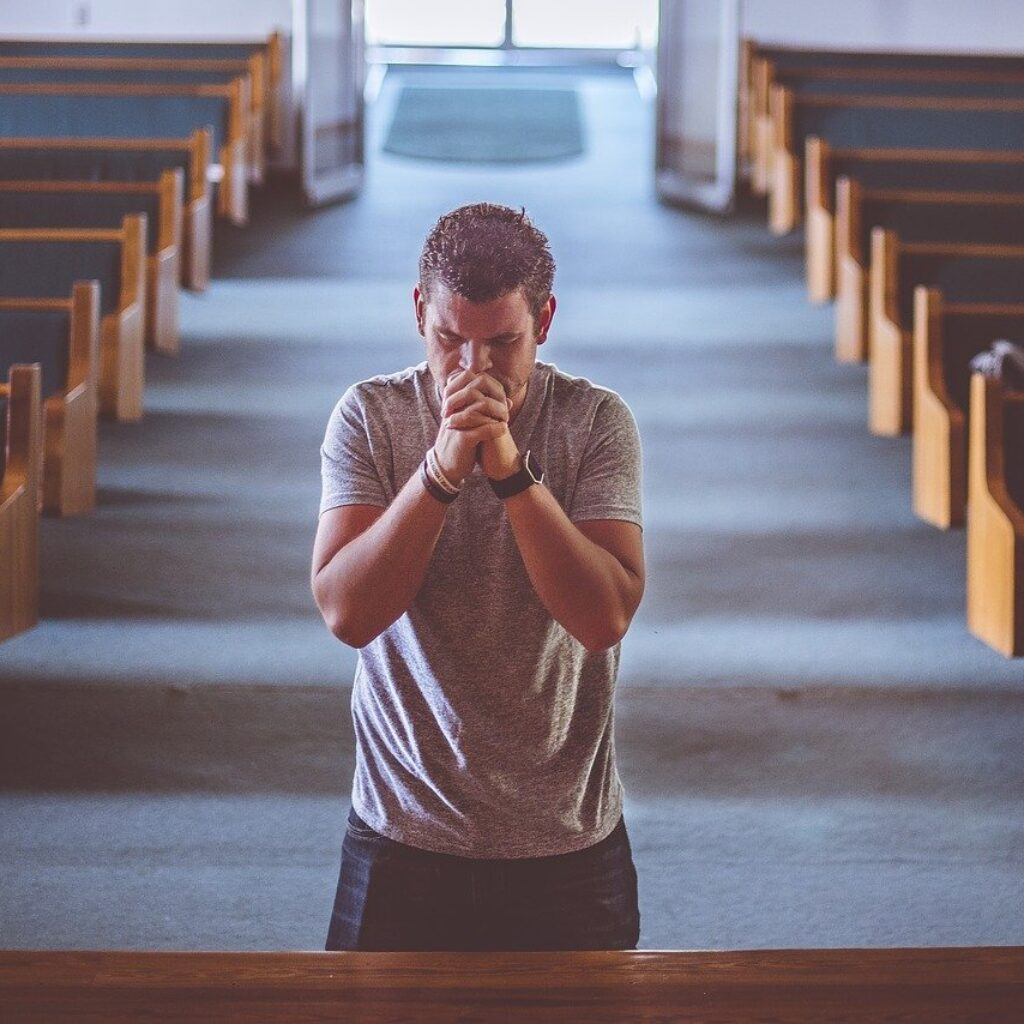 Man standing and praying in a church