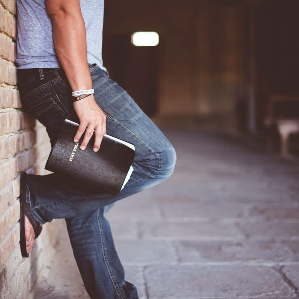 Person leaning on wall with Bible in his hand